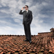 Businessman using binoculars on the rooftop of a house — Stock Photo #3388264