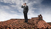 Businessman using binoculars on the rooftop of a house — Stock Photo