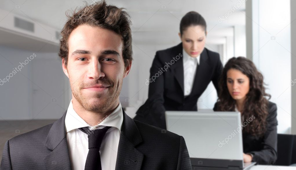 Smiling businessman with two businesswomen working on the background — Stock Photo #3382084