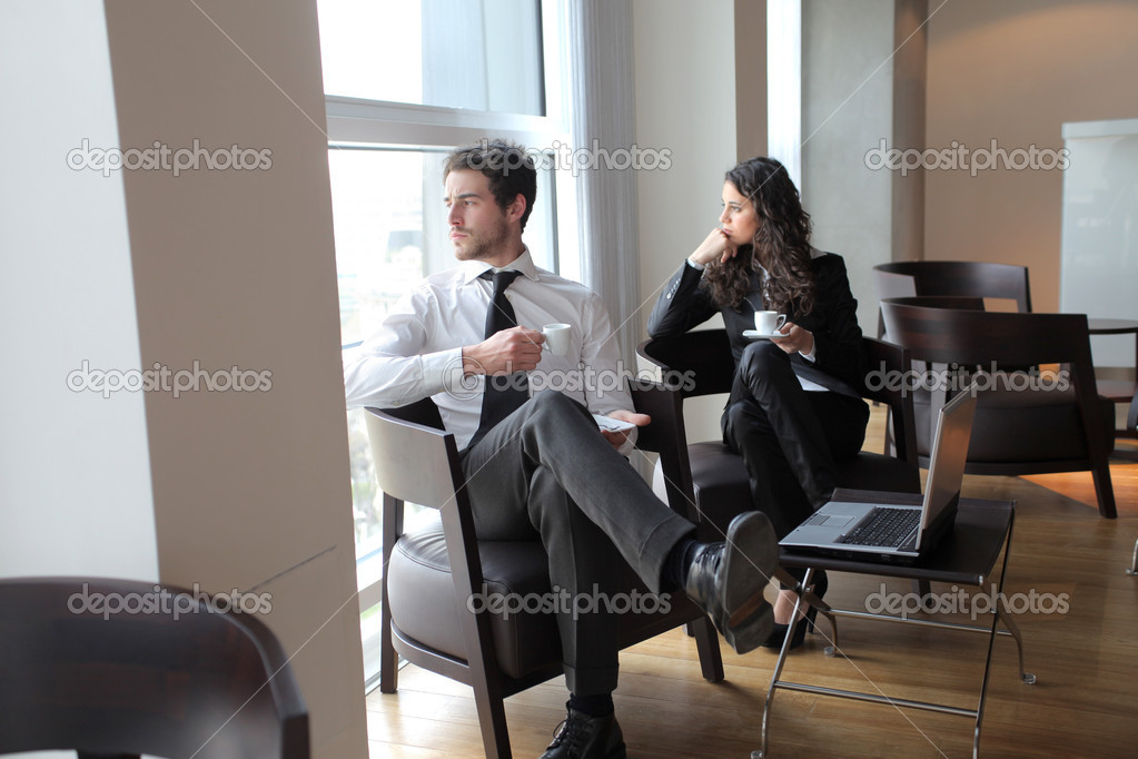 Two business sitting in a lounge and drinking coffee  Stock Photo #3388063
