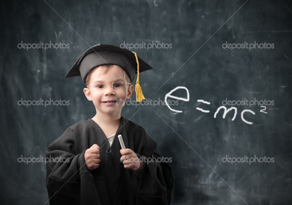 Smiling child in graduate uniform with a blackboard on the background — Stock fotografie #3388182