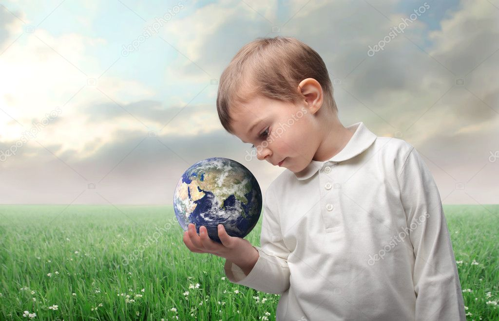 Child holding the earth with green meadow on the background — Stock Photo #3388520