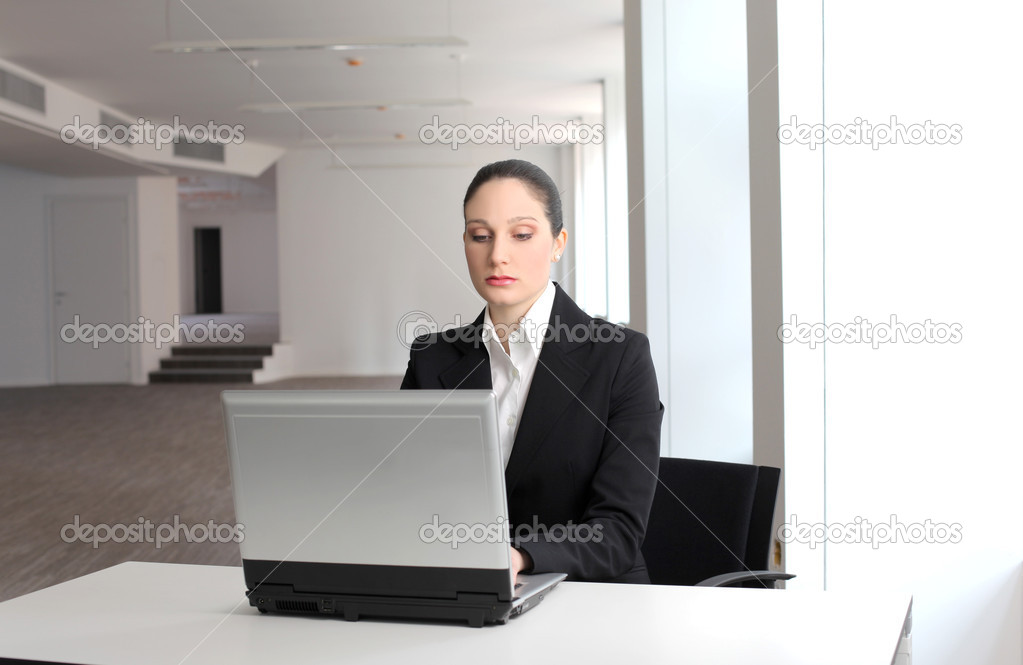 Businesswoman sitting and working on a laptop in an office — Stock Photo #3389678
