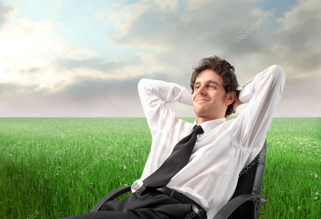 Smiling young businessman relaxing on a chair on a green meadow  Photo #3390235