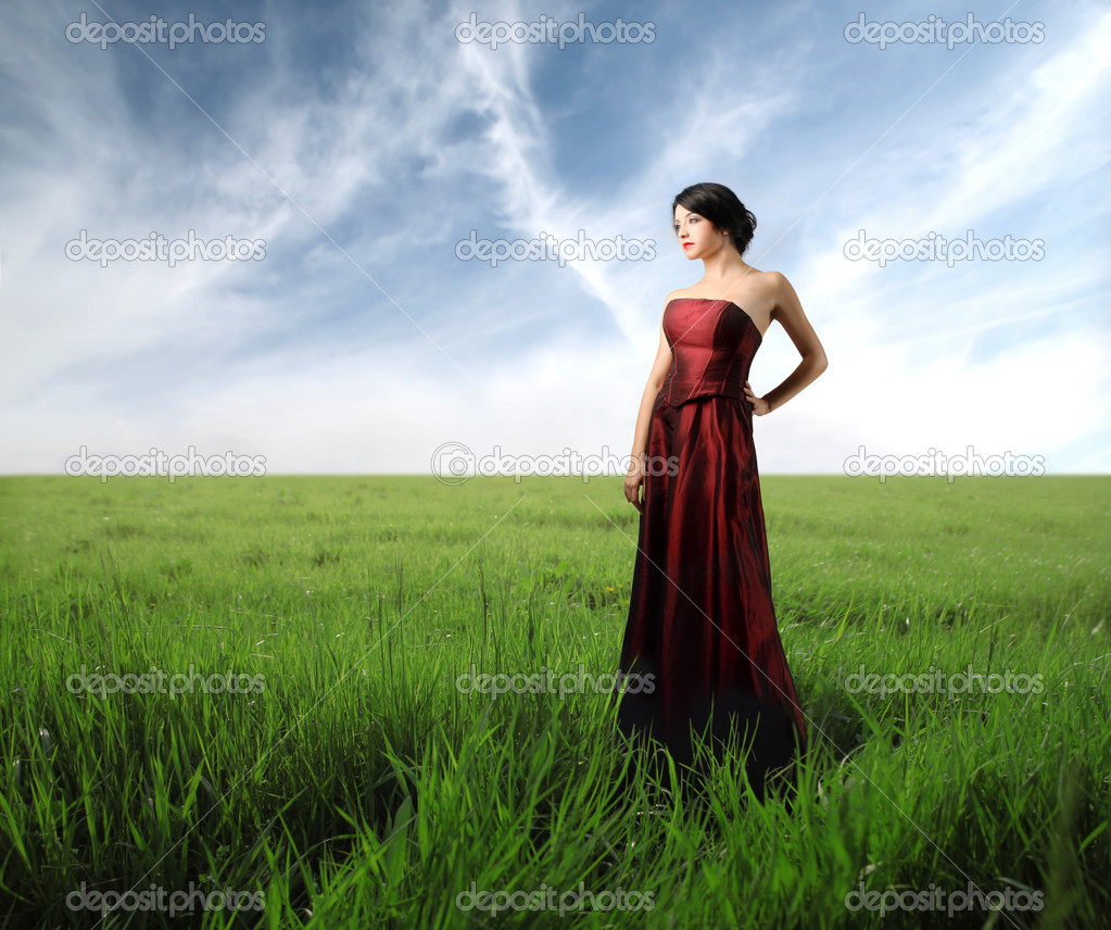Beautiful woman in wonderful dress standing on a green meadow — Stock Photo #3390336