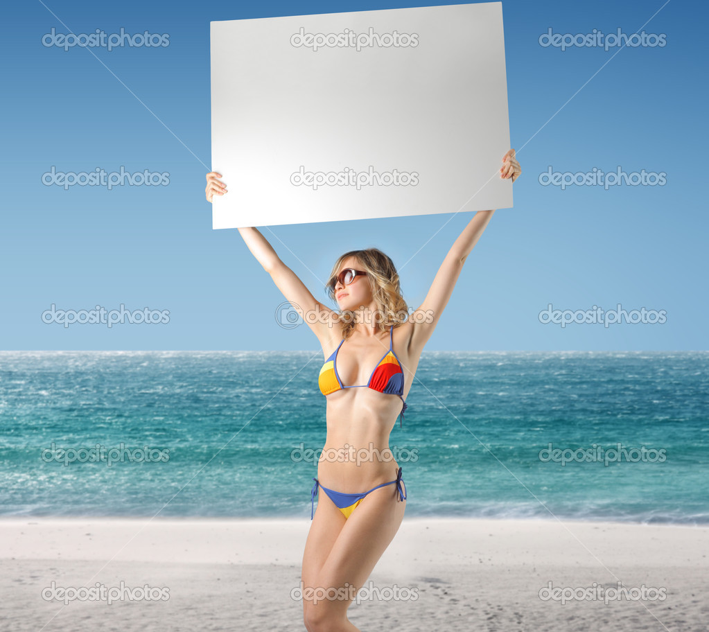 Beautiful woman at the beach holding a billboard — Stock Photo #3390503