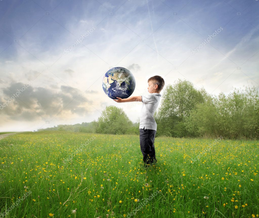 Child holding the earth on a green meadow — Stock Photo #3854906