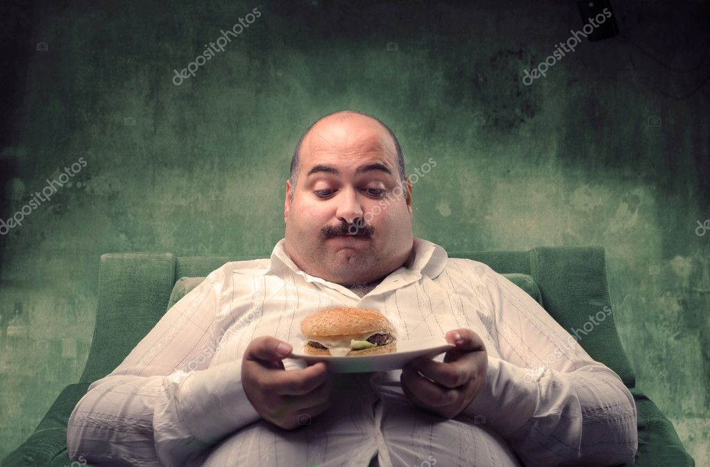 Fat man sitting in a couch and observing a hamburger — Stock Photo #3857239