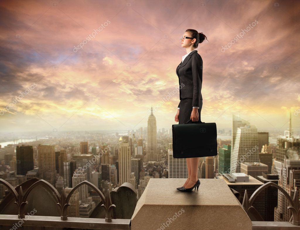 Young businesswoman standing on the rooftop of a skyscraper — Stock Photo #3857392