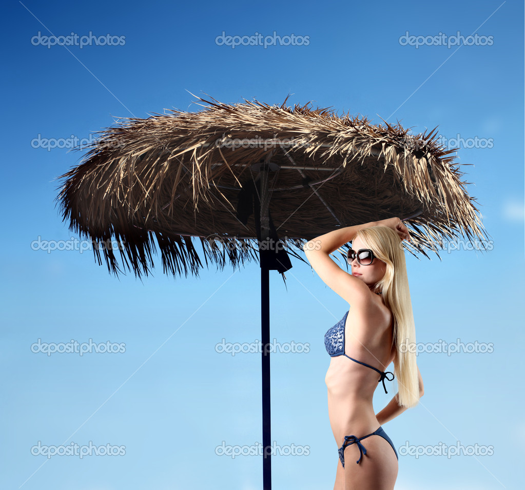 Beautiful woman in swimsuit standing beside an umbrella — Stock Photo #3857660