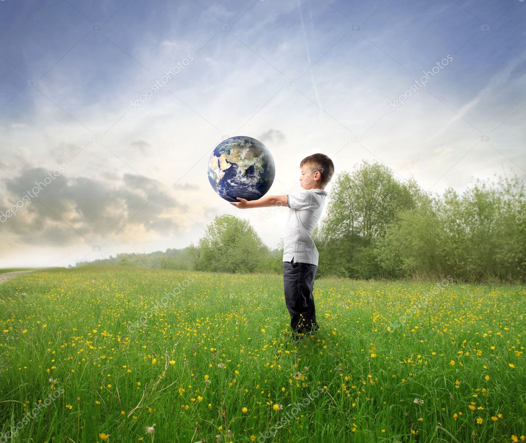 Child holding the earth on a green meadow  Stock Photo #3857837