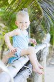 Toddler sitting on palm tree — Stock Photo