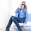 Woman wearing blue clothes sitting on sofa — Stock Photo