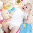 Baby girl lying down on playing mat — Stock Photo #3535139
