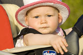 Portrait of baby girl sitting in a pram — Stock Photo
