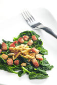 Fried spinach with bacon and pine nuts — Stock Photo