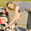 Woman with baby sitting in pram - Stock Photo
