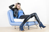 Woman wearing fashionable shoes sitting on sofa — Stock Photo