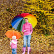 Mother and her daughter with umbrellas in autumnal nature — Stock Photo #3639300