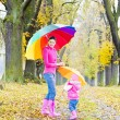 Foto Stock: Mother and her daughter with umbrellas in autumnal alley