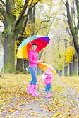 Mother and her daughter with umbrellas in autumnal alley — Стоковое фото
