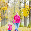 Stock Photo: Mother with her daughter in autumnal alley
