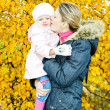 Portrait of woman with toddler in autumnal nature — Stock Photo