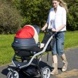 Womwith pushing pram — Stock Photo #3834436