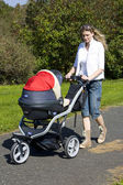Woman with pushing a pram — Stock Photo