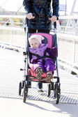 Woman with toddler sitting in pram on walk — Stock Photo
