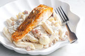 Baked salmon on pepper with creamy pasta — Stock Photo