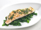 Grilled salmon with herbs on fried spinach — Stock Photo