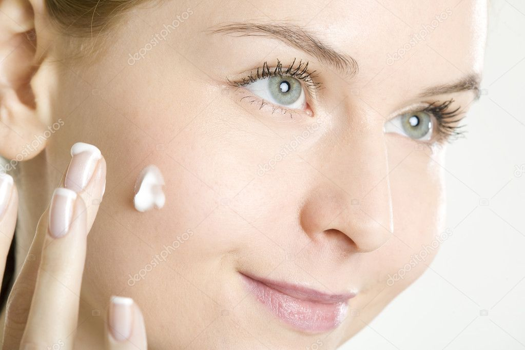 Portrait of woman putting cream on face — Stockfoto #3942435