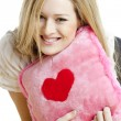 Woman holding a pillow with heart — Stock Photo