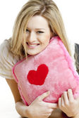 Woman holding a pillow with heart — Stok fotoğraf