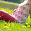 Pregnant woman on meadow - Stock Photo