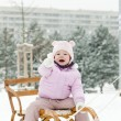Little girl sledding in snow - Stock Photo