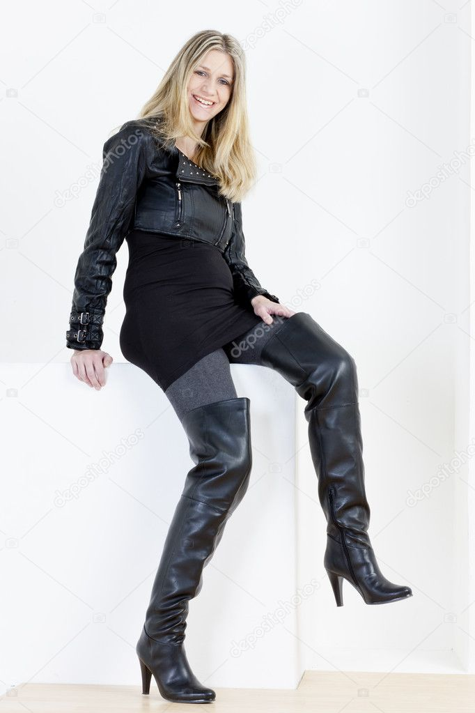 Cool Standing Woman Wearing Black Dress And Black Boots Stock Photo