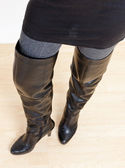 Detail of standing woman wearing fashionable black boots — Stock Photo