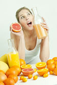 Woman with citrus fruit and orange juice — Stock Photo