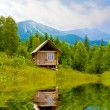 Wooden house in mountains near lake — Stock Photo #2820308