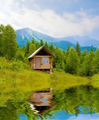 Wooden house in mountains near lake — Stock Photo