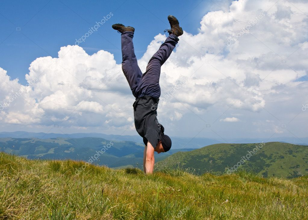 Happy man stay head over heels on meadow in mountains — Stock Photo #2952902