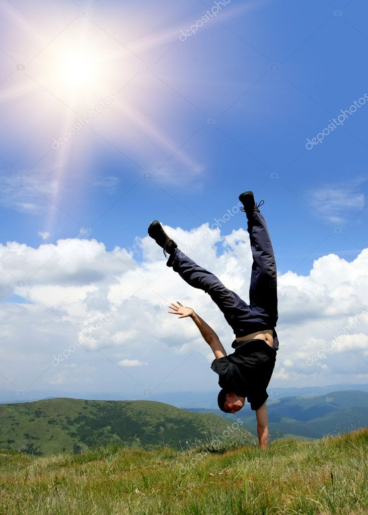 Happy man in mountains stay head over heels on hand  — Stock Photo #2952906