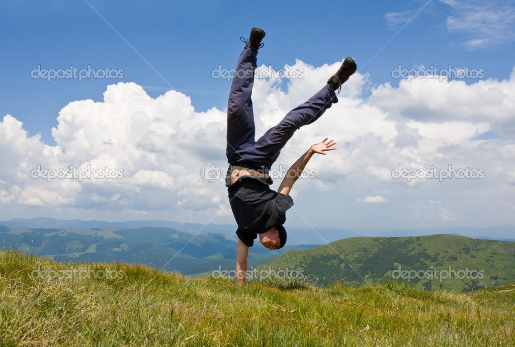 Happy man in mountains stay head over heels on one hand — Stok fotoğraf #2952913