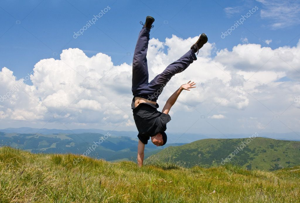 Happy man in mountains stay head over heels on one hand — Stock fotografie #2952913