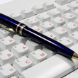 Pen on office computer keyboard — Stock Photo