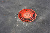 Red sewer manhole — Stock Photo