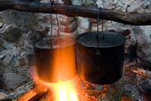 Two tourists kettles on campfire — Stock Photo