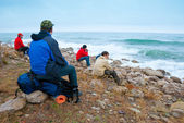 Hikers on a stony sea shore — Stock Photo